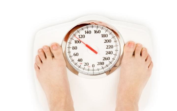 Person weighs themselves on weighing scales