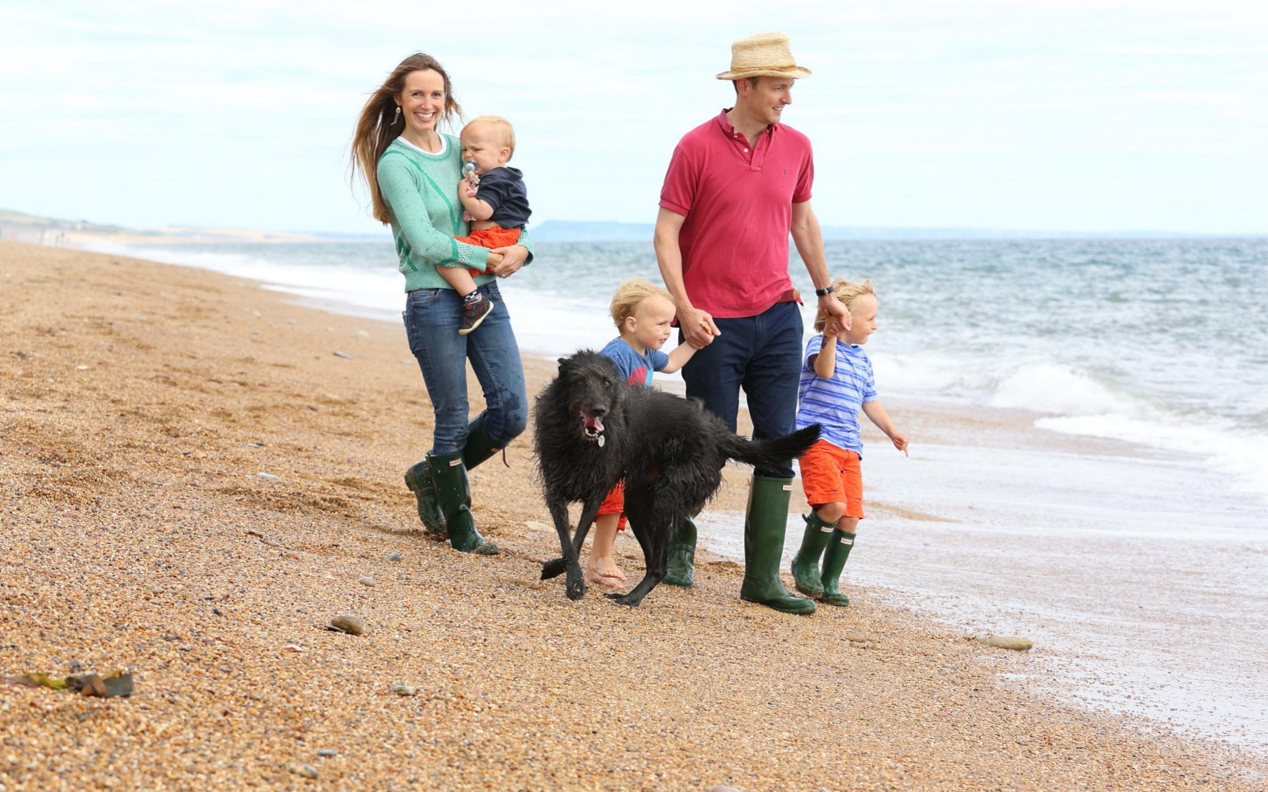 Anna Tyzack and family, husband Christian and sons Hector (4), Alfred (3), Horatio (18mths), with dog Lowly on the beach at Burton Bradstock in Devon