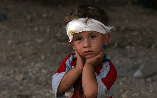 An Iraqi Yazidi child, whose family fled their home a week ago when Islamic State (IS) militants attacked the town of Sinjar, looks on at a makeshift shelter in the Kurdish city of Dohuk