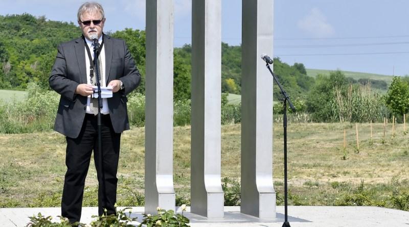 Féhr György, a Paksi Német Nemzetiségi Önkormányzat elnöke beszédet mond a kitelepítési emlékműnél Dunakömlődön. Fotó: Szaffenauer Ferenc/Paksi Hírnök