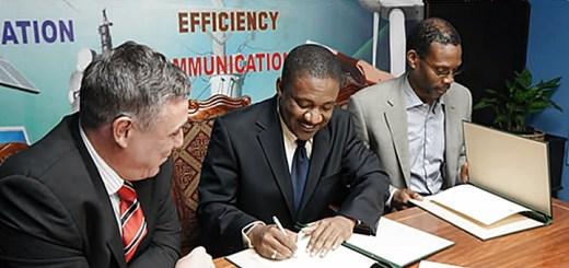 Phillip Paulwell, ministro de Ciencia, Tecnología, Energía y Minería firma el acuerdo para la renovación de la licencia de Digicel, rodeado por Barry O'Brien, CEO de Digicel izquierda) y Garfield Sinclair, CEO de Lime (derecha). Imagen: MSTEM.