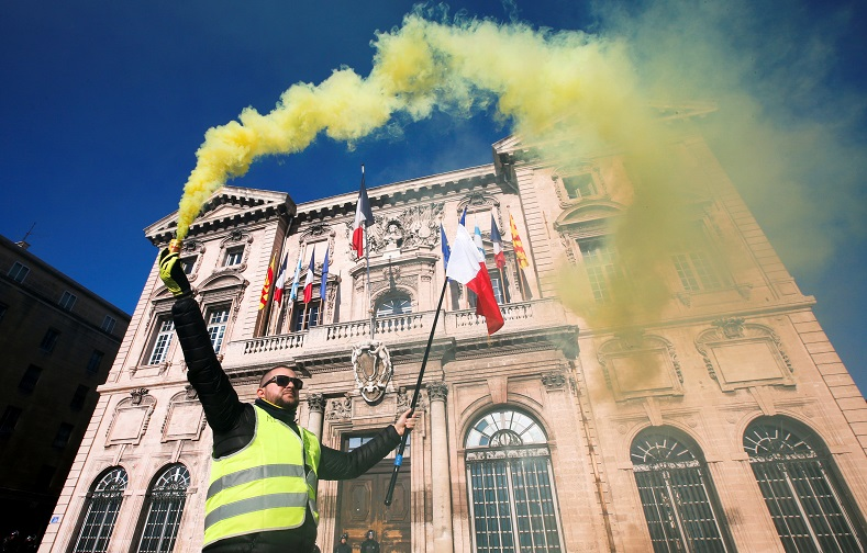 A protester wearing a yellow vest holds a flare in front of the town hall in Marseille.