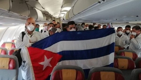 Cuban health workers hold a flag of their country inside an airplane bound for Italy, March, 2020.