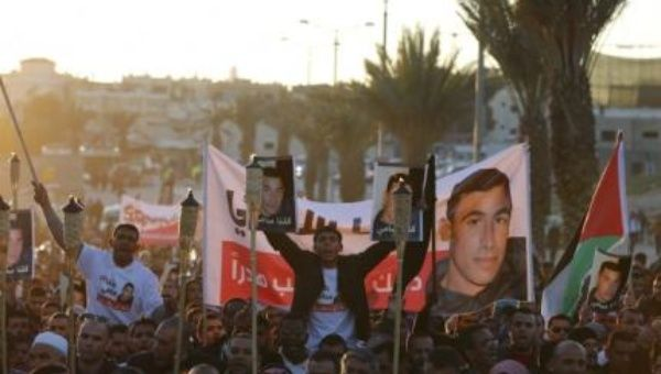Israeli Arab protesters hold torches and posters of Sami al-Jaar, who was shot dead by police officers last week, during a protest in the southern town of Rahat.