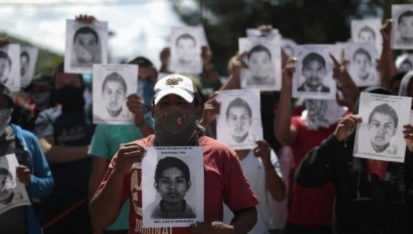Students from Ayotzinapa Teachers Training College Raul Isidro Burgos hold pictures of missing students outside the General Attorney building in Chilpancingo, in Guerrero, Oct. 7, 2014.