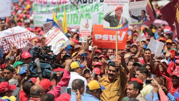 President Nicolas Maduro holds a sign of former President Hugo Chavez at a rally in Bolivar state, Feb. 25, 2015.