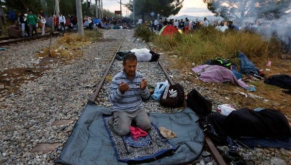 A Syrian refugee prays on a rail track at the Greek-Macedonian border, near the village of Idomeni, August 22, 2015