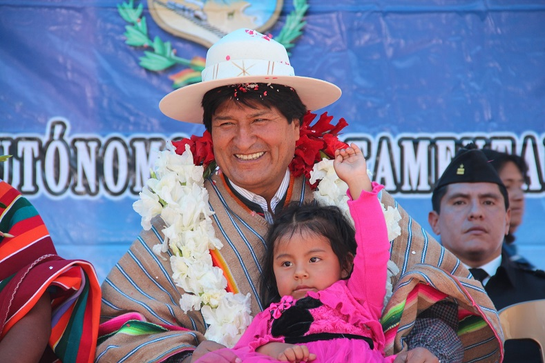 The president holds a child during a public event in La Paz, Bolivia. The government of Evo Morales has dramatically improved the education and food security of millions of children.