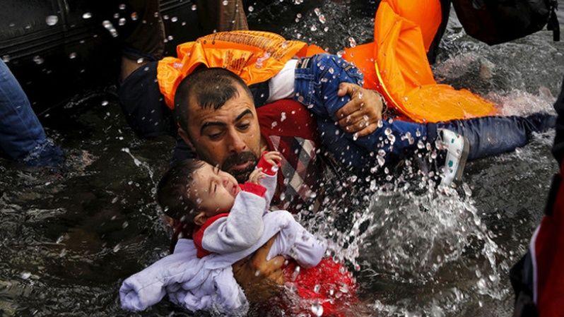 Un refugiado sirio se aferra a sus hijos mientras lucha por bajar de un bote en la isla griega de Lesbos.