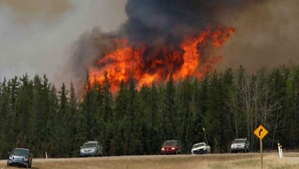 A wildfire burns as evacuees who were stranded north of Fort McMurray, Alberta, Canada head south of Fort McMurray on Highway 63.