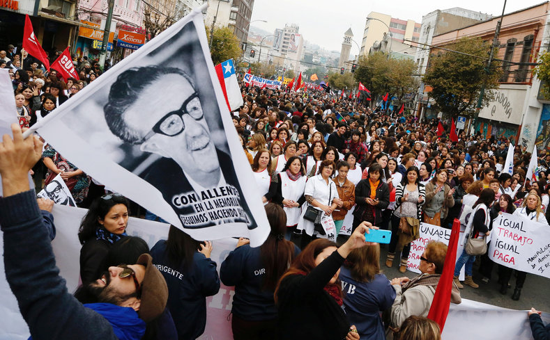 A man holds a sign with the image of Chile