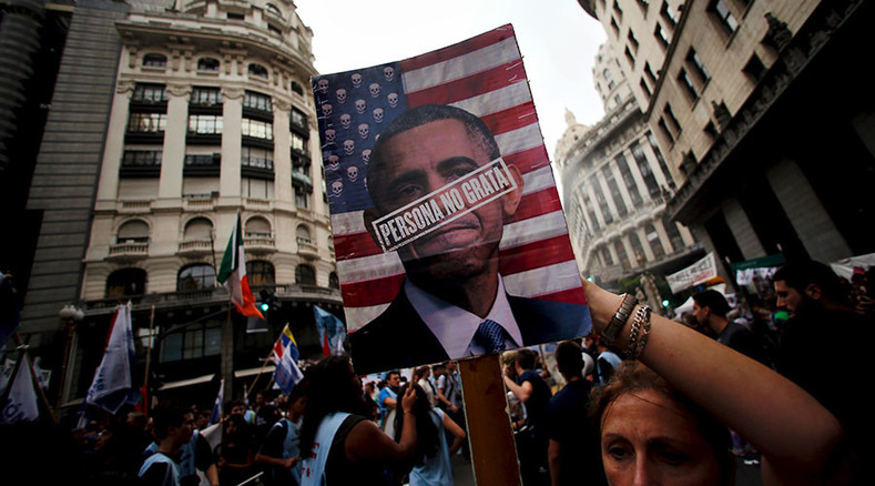 "A woman holds up a portrait of U.S. President Barack Obama with the words ""persona non grata"" during a demonstration to commemorate the 40th anniversary of Argentina"