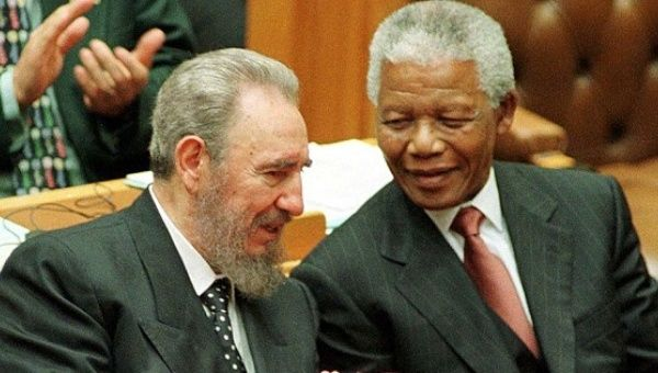 Cuban President Fidel Castro chats with President Nelson Mandela after addressing the South African Parliament on September 4, 1998.