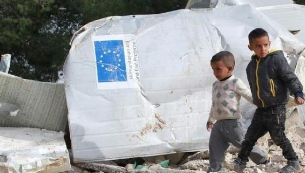 Palestinian boys walk past the remains of their house, which was funded by the EU