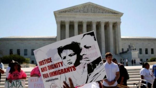Demonstrators from the immigrant community advocacy group CASA carry signs as they march in the hopes of a ruling in their favor on decisions at the Supreme Court building in Washington, U.S. June 20, 2016.