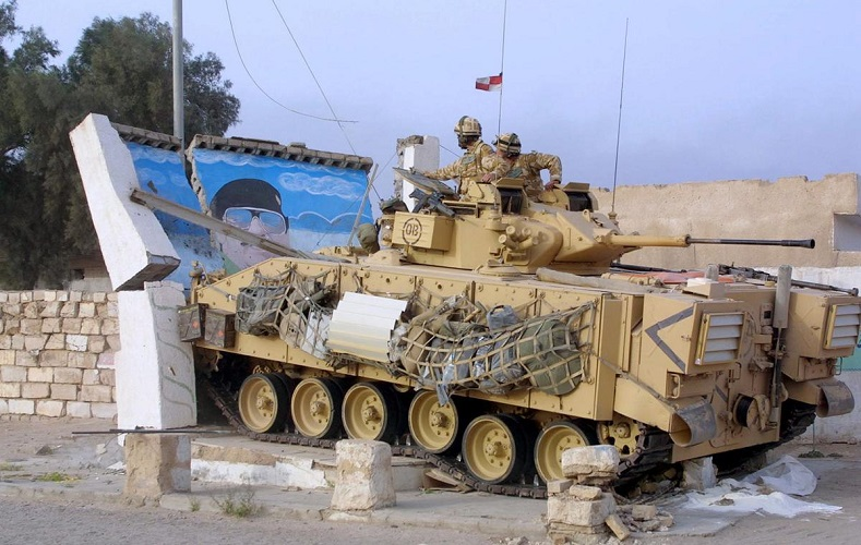 A British Warrior armored combat vehicle knocks over a picture of Saddam Hussein in the city of Basra, in southern Iraq, on March 24, 2003.