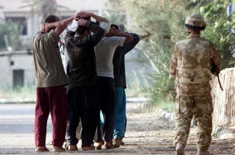 A British soldier guarding Iraqi prisoners in 2003. Graphic photographs of the Iraqis that British soldiers are said to have