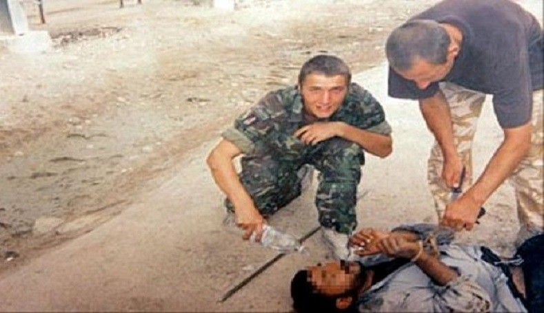 This is a picture released by a British Court Martial, Tuesday, Jan, 18, 2005, in Osnabrueck, Germany allegedly showing Corporal Daniel Kenyon, top right, in the brown t-shirt, leaning over an Iraqi detainee.