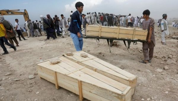 Afghan men carry empty coffins for the victims of yesterday