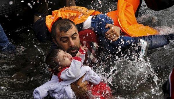 Un refugiado sirio se aferra a sus hijos mientras lucha por salir de un bote en la isla griega de Lesbos, después de cruzar desde Turquía.