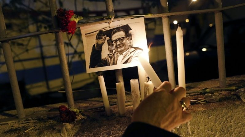 A person lights a candle in tribute to Salvador Allende.
