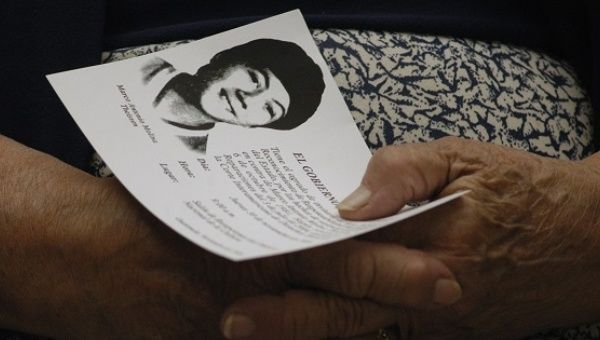 A family member holds an image of Marco Antonio Molina Theissen, kidnapped and disappeared in 1981 when he was 14 years old.