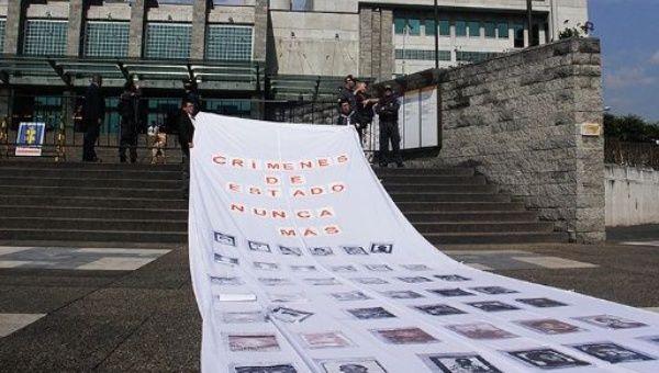 """Los defensores de los derechos humanos en Colombia despliegan pancarta que dice: """"Crímenes de Estado, nunca más."""""""