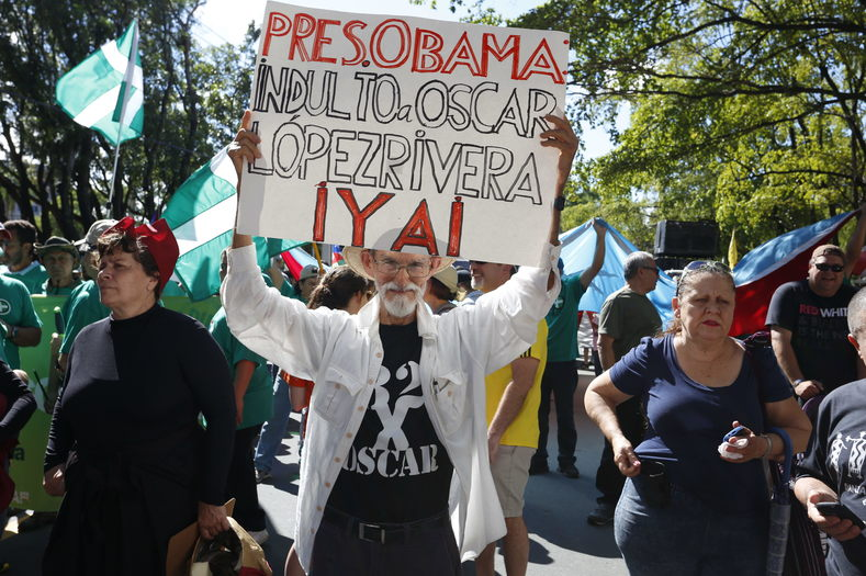 "A man holds a sign reading, ""President Obama Free Oscar Lopez Now!"" at a rally in Puerto Rico."