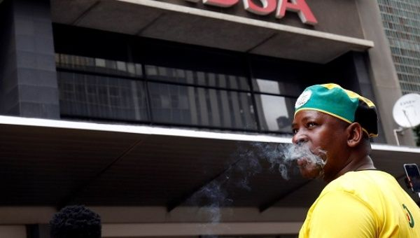 A member of the African National Congress Youth League protests in front of ABSA Bank against an apartheid-era bailout, Jan. 26, 2017.