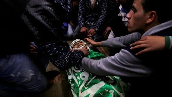 Mourners gather around the body of Palestinian Mohammed Abu Khalifa during his funeral in the Jenin refugee camp in the West Bank, Jan. 29, 2017.