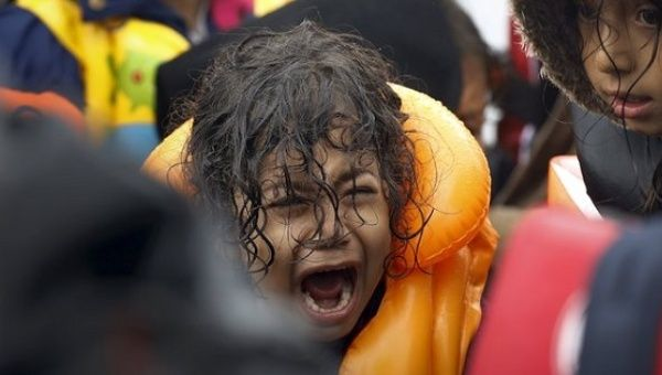 A Syrian refugee child screams inside an overcrowded dinghy after crossing part of the Aegean Sea from Turkey to the Greek island of Lesbos Sept. 23, 2015.