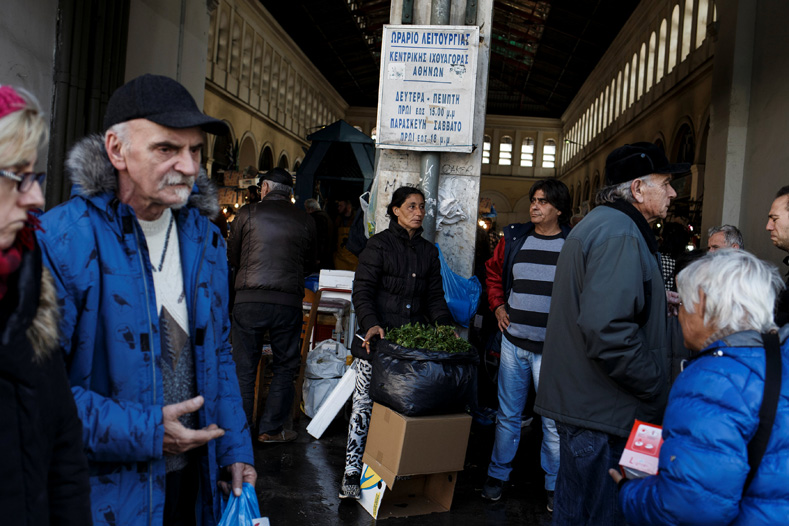 People make their way outside the main fish market of Athens, Greece, Feb. 18, 2017.