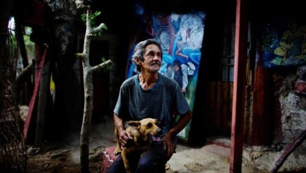 Artist Remigio Hernandez, 64, sits with his dog at his self made