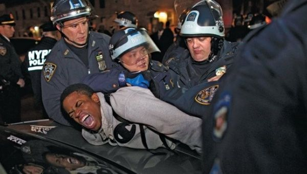 Cops arrest an activist peacefully protesting the police shooting of 16-year-old Kiki Gray in New York City, 2013.