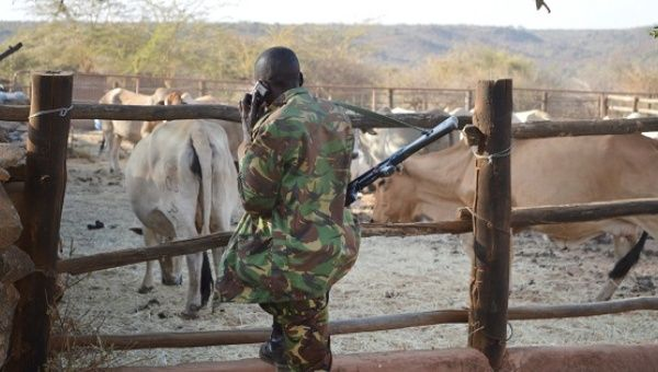 A Kenyan police officer talks on his mobile phone after he and his colleagues deployed to guard Sosian ranch.