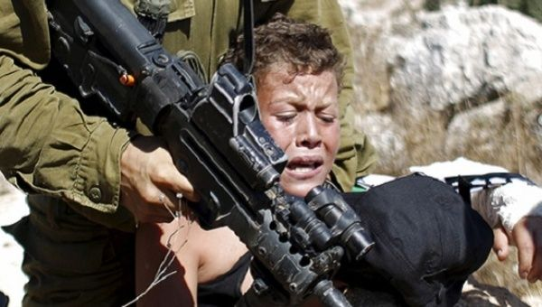 An Israeli soldier detains a Palestinian boy during a protest against Jewish settlements in the West Bank village of Nabi Saleh, near Ramallah, Aug. 28, 2015.
