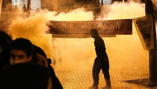 "Anti-riot police throw tear gas as a man stand next to a banner reading ""Police murderer, Do justice."""