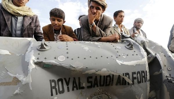 People stand by part of a Saudi fighter jet found in Bani Harith district north of Yemen