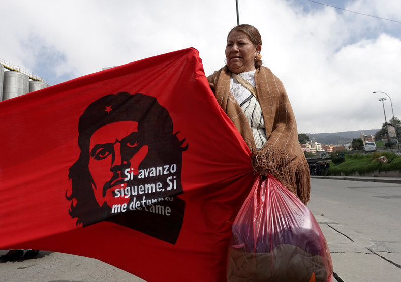 """A retailer of second hand clothes attends a rally during May Day celebrations in La Paz, Bolivia May 1, 2017. The banner reads """"If I advance, follow me, if I stop, kill me""""."""