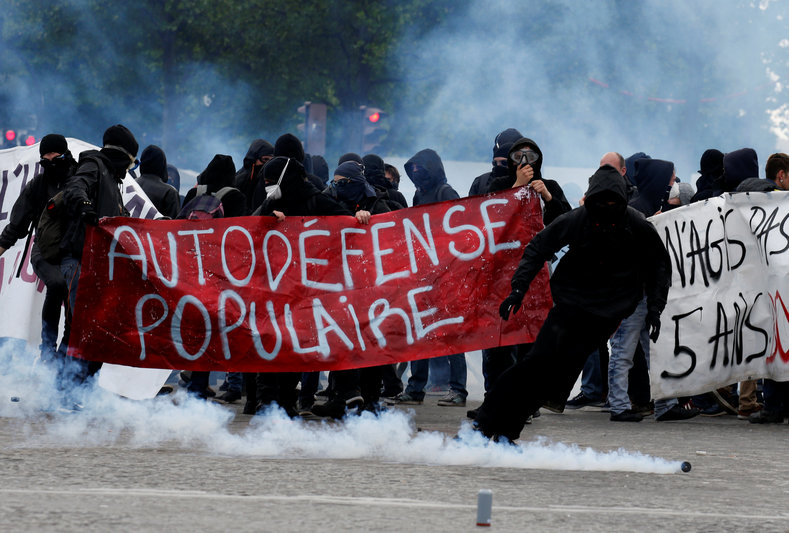 """Tear gas floats in the air as demonstrators walk behind a banner which reads, """"Populist Self-Defence"""" during clashes at the traditional May Day labour union march in Paris, France, May 1, 2017."""