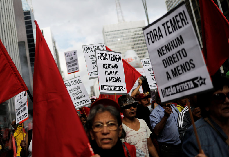 Trade unionists take part in a demonstration against Brazil
