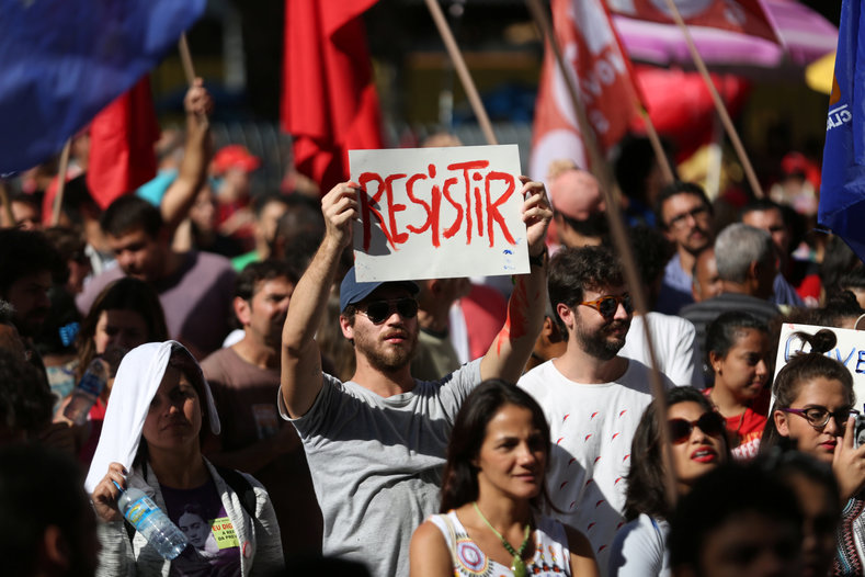 "A man holds a sign reading ""To resist"" during a demonstration against Brazil"