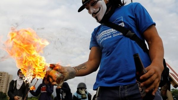 A demonstrator prepares to throw a molotov cocktail while rallying against Venezuela