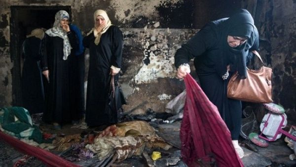 Palestinian women look at the damage at the Dawabsha family