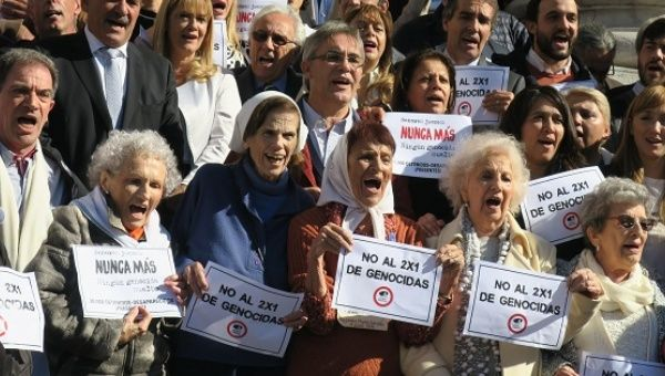 """Members of human rights organizations outside Congress in Buenos Aires to celebrate a sanction against the so-called """"two for one"""" bill."""