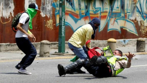 Demonstrators grab a riot police officer at a rally against Venezuela