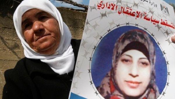 The mother of Hana Shalabi, a hunger-striking Palestinian prisoner, holds up an image of her daughter.
