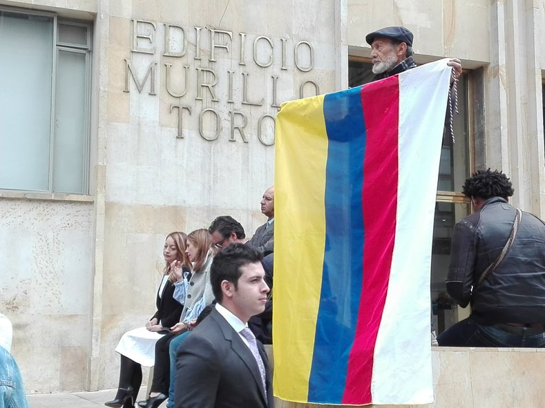 A man holds the Colombian flag with an extra white stripe added to represent peace.