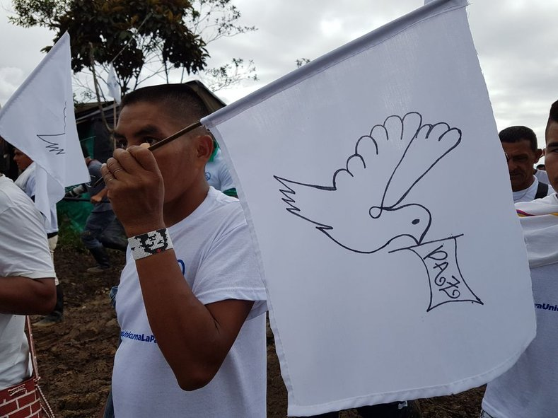 A FARC member holds a sign with the image of a dove, celebrating the historic chapter in the peace agreement between the FARC and the Colombian government.