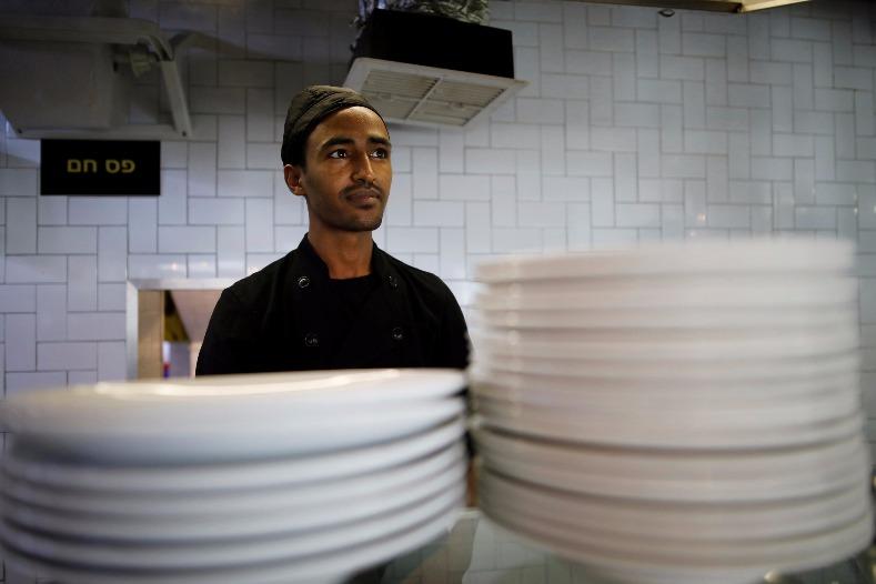 Teklit Michael, 29, an asylum seeker from Eritrea, works in the kitchen of a restaurant in Tel Aviv, Israel June 25, 2017.